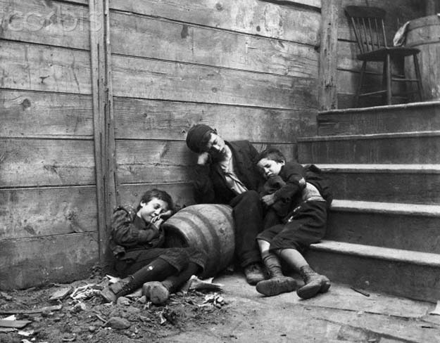 Three homeless boys sleep on a stairway in a Lower East Side alley