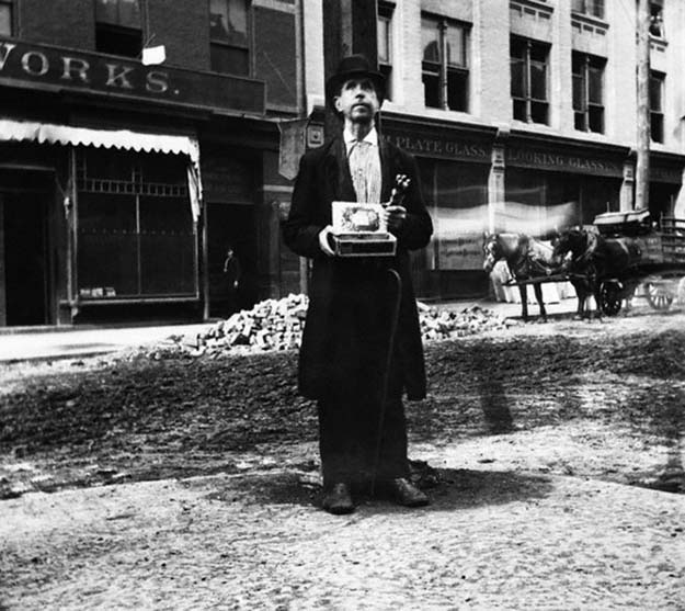 A blind man stands alone on a street corner, offering pencils for sale