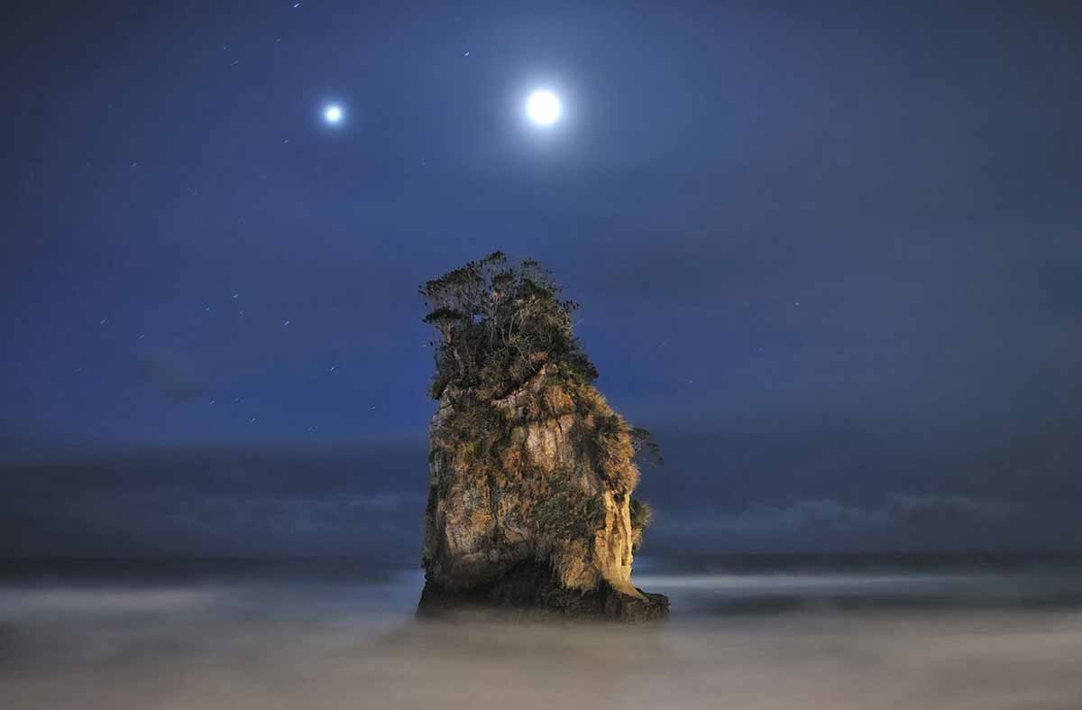 Jupiter and the Moon above a rock formation; Japan