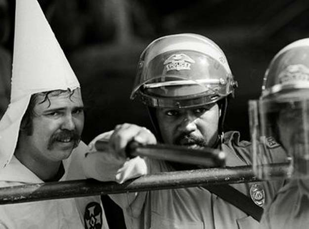 Police officer protects a KKK member from protestors