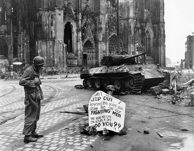 Corporal Luther E. Boger of US 82nd Airborne pision reading a warning sign, Cologne, Germany, 4 April 1945