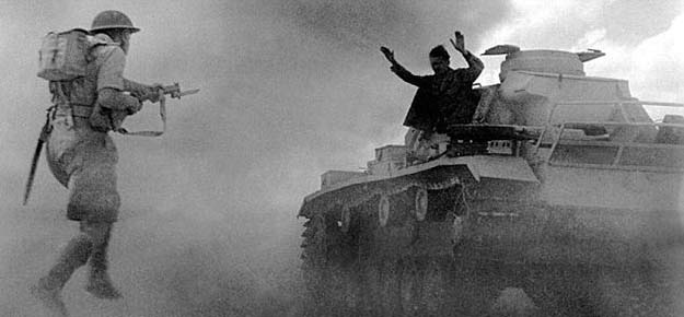 A Panzer III tank crewman surrenders to an advancing Brittish soldier during the Battle of El Alamein, 1942.