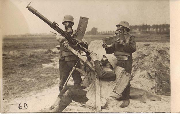 Three German soldiers in body armor and gas masks demonstrate operating a 2cm Becker-Flugzeugkanone, an anti-aircraft gun, Western Front, circa 1918