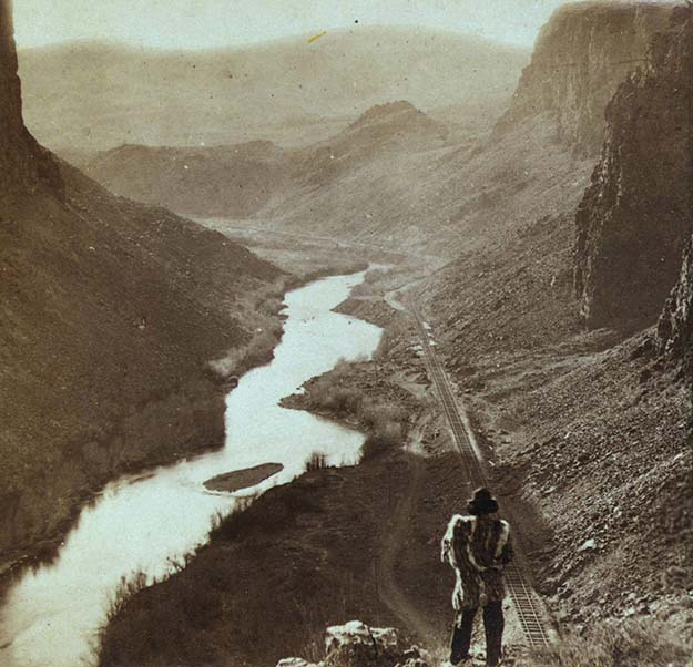 A Native American looks down at a newly-completed section of the transcontinental railroad. Nevada, about 1868
