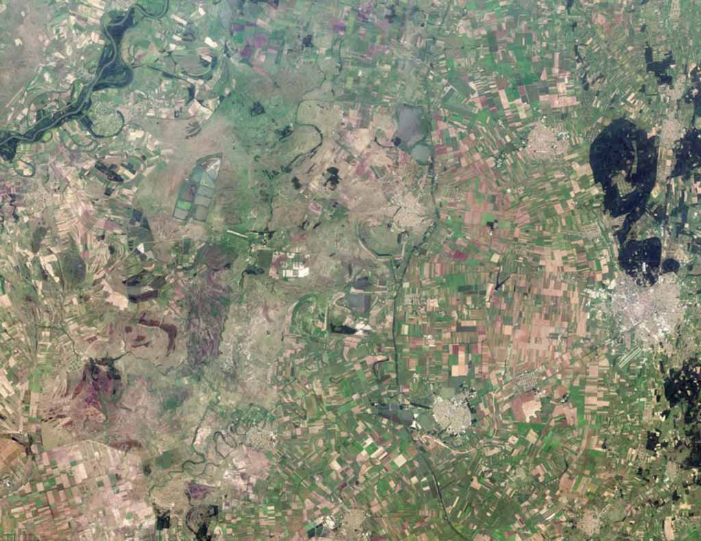 Agricultural fields radiate away from the well-defined outer boundaries of Hungary. The dark areas on the right are dense forests.