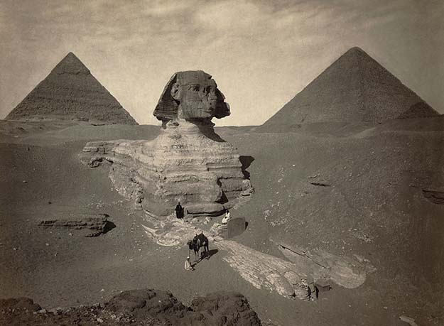 A late nineteenth century photo of the partially excavated Great Sphinx of Giza, with the Pyramid of Khafre (left) and the Great Pyramid of Giza (right) behind it