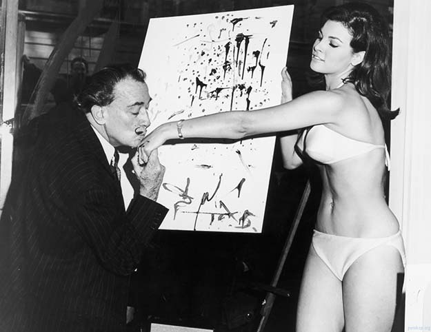 Salvador Dalí kisses 25-year-old Raquel Welch's hand in front of his abstract portrait of her, 1965