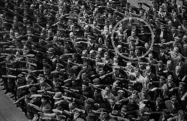 "A lone man refusing to do the ""Sieg Heil"" salute at the launching of the Horst Wessell in Nazi Germany, 1936"