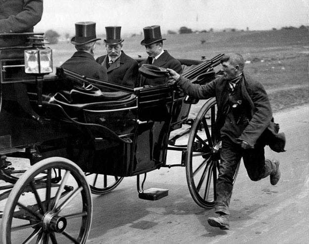 A beggar running alongside King George V's coach. England, c. 1920