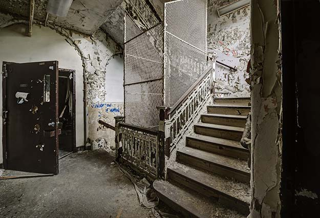 Stair well of abandoned asylum NY complete with suicide cages