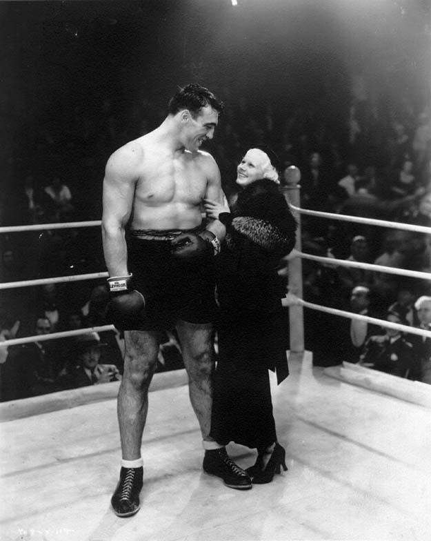 Actress Jean Harlow poses with boxer Primo Carnera, 1933