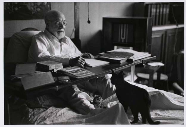 Matisse working in bed, his cats at his feet; Nice, France,1949