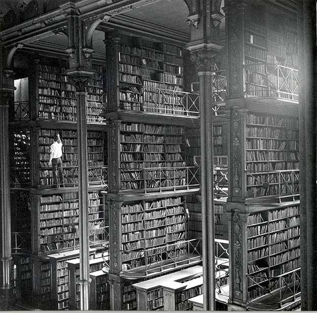A man browsing for books in Cincinnati's cavernous old main library. The library was demolished in 1955