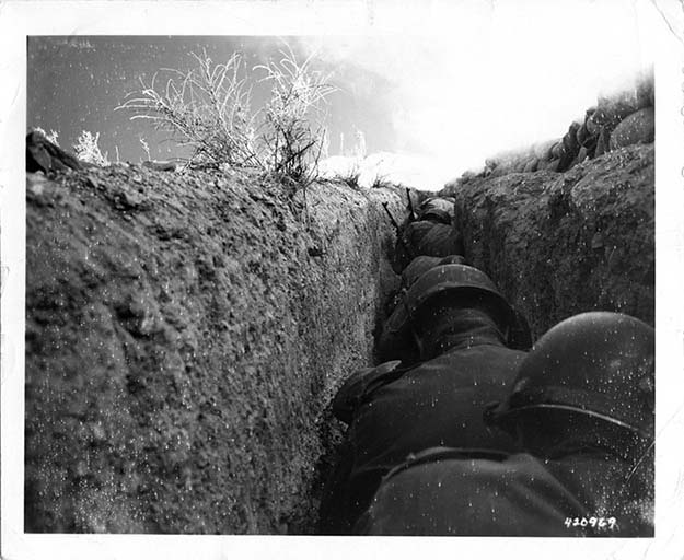 American soldiers shelter in a trench just over a mile from ground zero moments after the detonation of the 43 kiloton nuclear device Simon at the Nevada Test Site, 1953