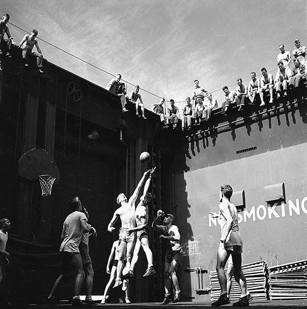 Gerald Ford (left jumper), future 38th US President, playing basketball in elevator well of light aircraft carrier USS Monterey, 1944