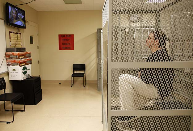 Cory Adams watches a movie from a cage in the medical facility at San Quentin state prison