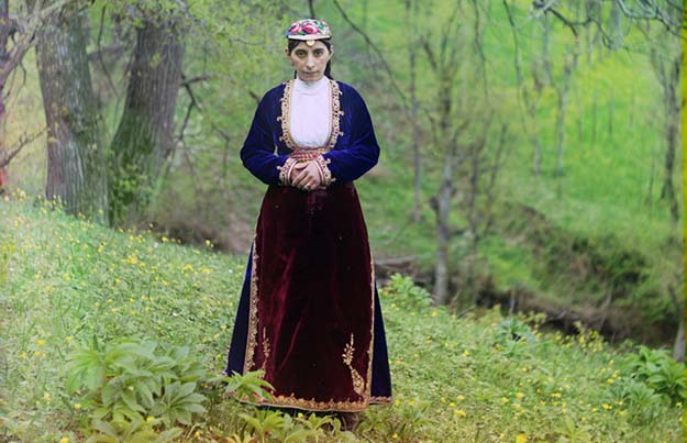 An Armenian woman in national costume poses for Prokudin-Gorskii on a hillside near Artvin (in present day Turkey)
