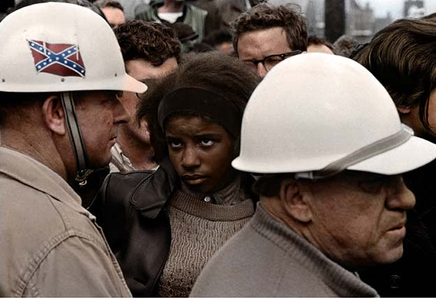 A Civil Rights demonstration in the 60s, an african-american woman stares down a man donning the Confederate flag on his hard-hat, Bob Adelman photograph