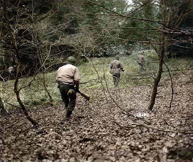 American G.I.'s from the First Army hunt German paratroopers dropped during the Battle of the Bulge somwhere in Belgium, Dec. 18, 1944