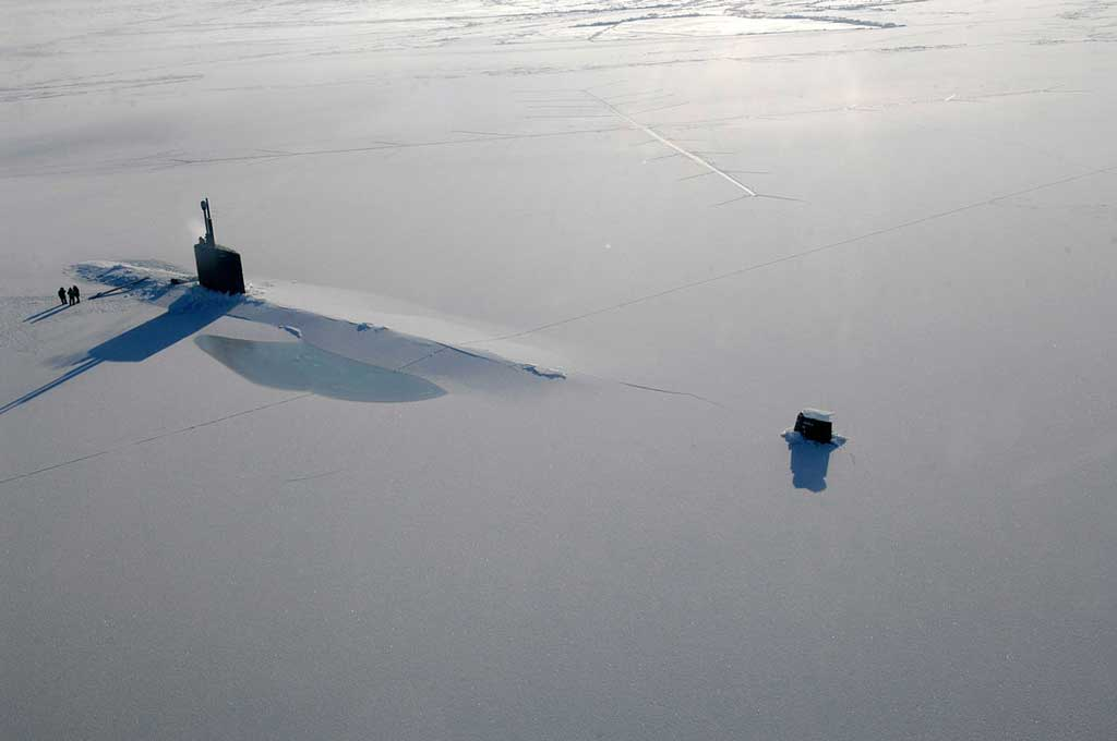 a submarine surfaces through arctic ice
